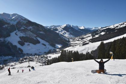 A solo snowboarder on a piste just above Saalbach