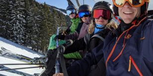 Skiers on a lift telling solo ski holidays stories and experiences