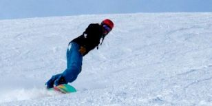 An individual snowboarder mastering her new skills